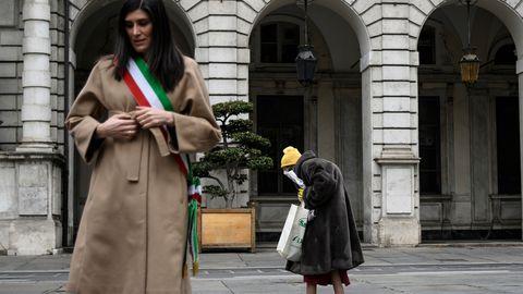 31.märts 2020, Turin, Itaalia. Linnapea Chiara Appendino seisatab vaikuseminutiks, mil linn mälestab viiruseohvreid, taustal kõnnib eakas Itaalia kodanik.