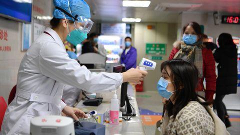 Hiina medtöötaja mõõtmas kehatemperatuuri, et teha kindlaks haiged inimesed, eelkõige need, kellel on uus koroonaviirus